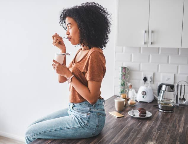 Young woman sitting on the kitchen bench eating probiotic rich yoghurt