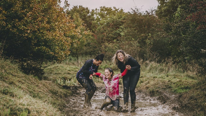 Three women are laughing in the mud, two of them are helping their friend up. It looks like they are doing an obstacle course. The perfect resilience skills training activity.