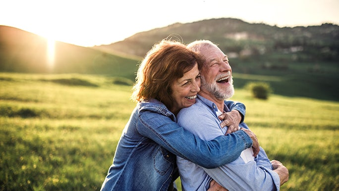 A couple embrace on a grassy hill, the sun is setting behind them and they look happy and healthy.