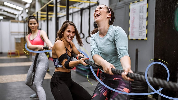 Three female friends working out in the gym pulling a combat rope