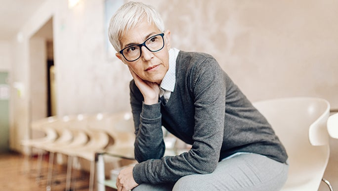 A lady with a grey pixie cut and black-framed glasses looks concerned. It seems as though she is in some sort of waiting room and may have lockdown fatigue.