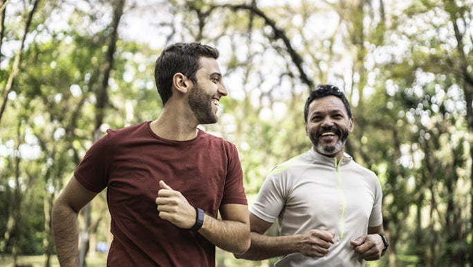Two men run through a park together, they exercise weekly to stay healthy.