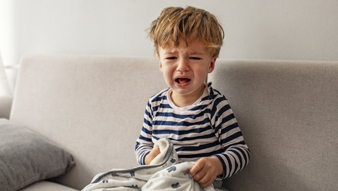 A little boy is crying on the couch, he is holding a blanket.