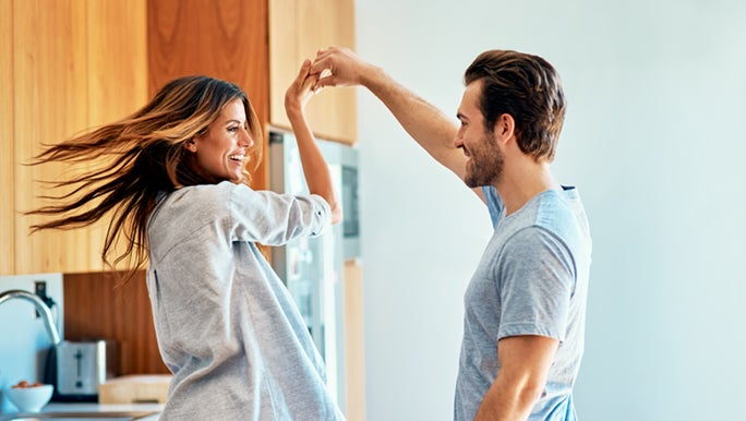 A couple are enjoying the positive mental effects of music. He is spinning her in the kitchen and they are laughing.