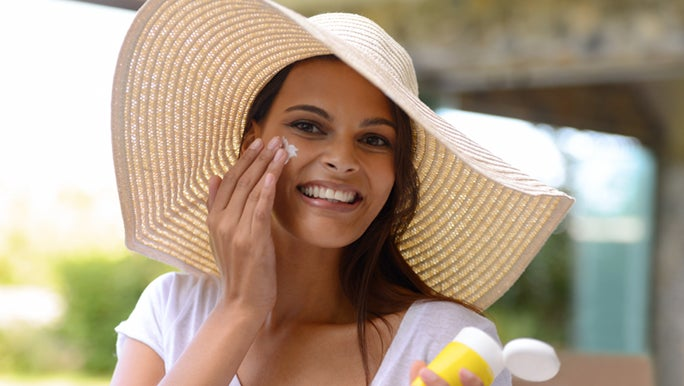 A lady is outside wearing a sunhat, and applying sunscreen before she leaves. Sunscreen is one of the ways to fight adult acne.