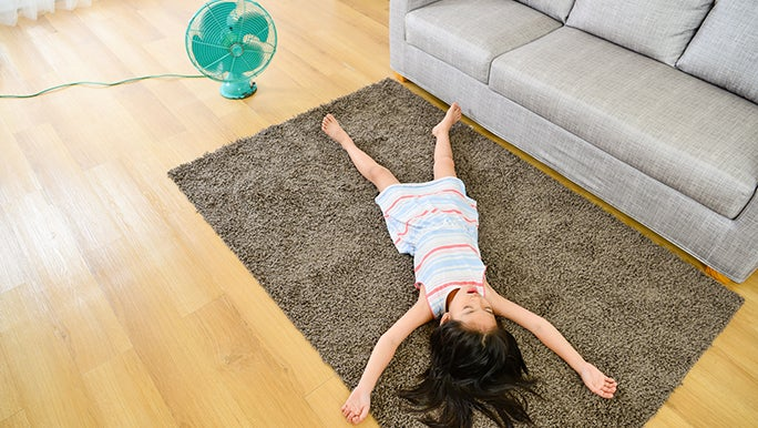 A little girl lays on a rug with her limbs outstretched in the living room. There is a fan on the floor near her.