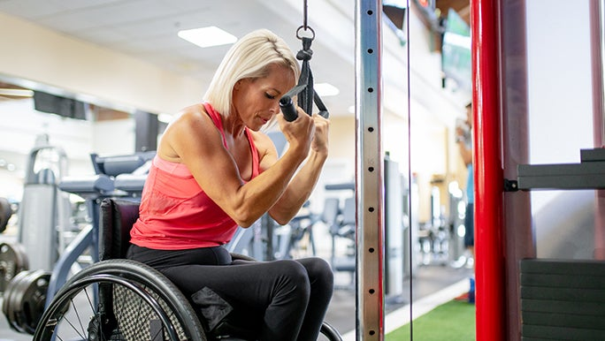 Woman in a wheelchair with silver hair using a weights machine. She is doing reps to build muscle.