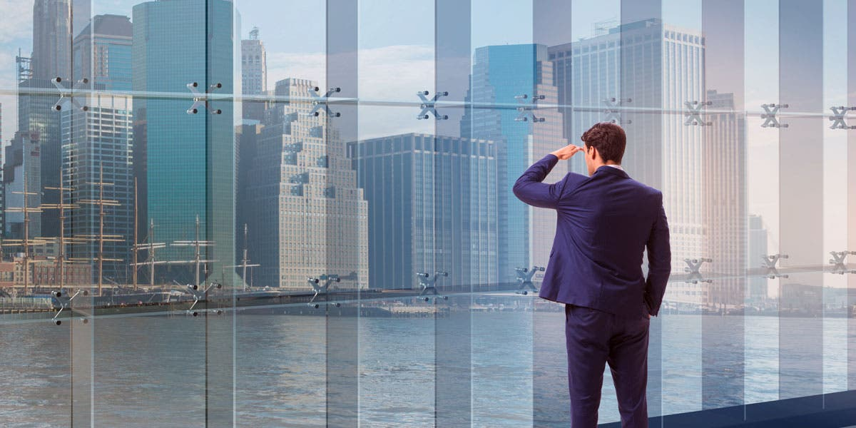 man in a suite looking out a window at a city
