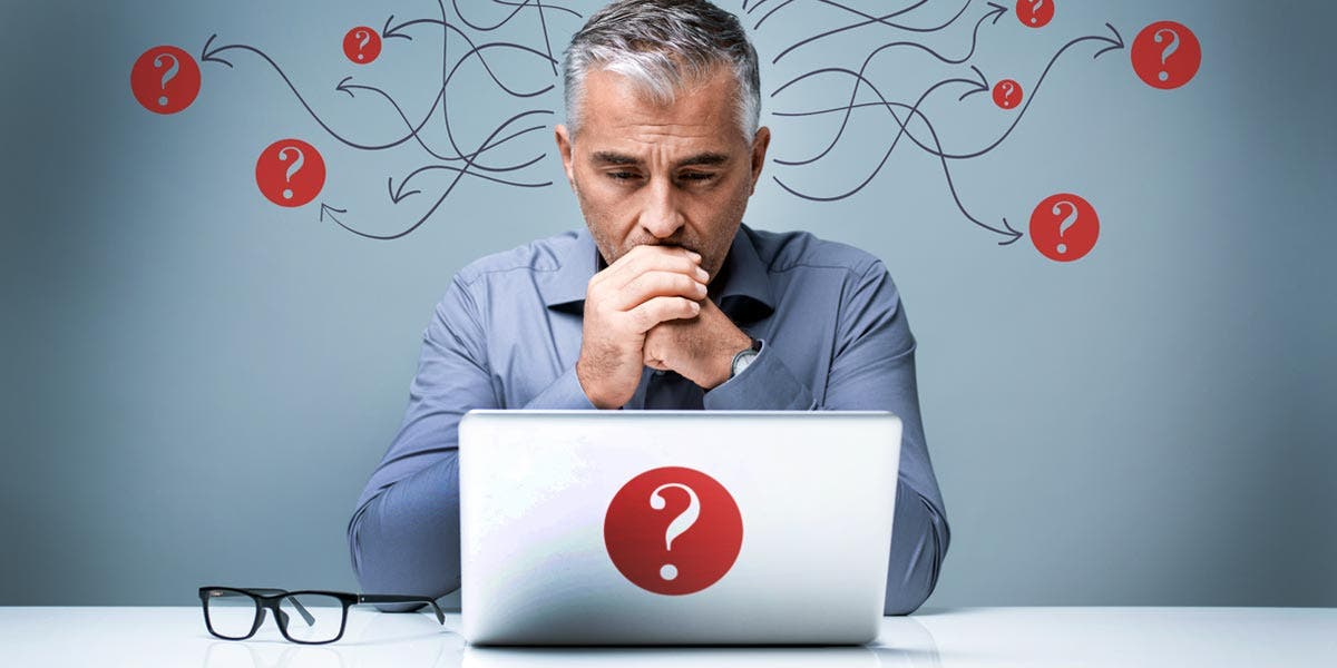 a man looking at a laptop with question marks around him