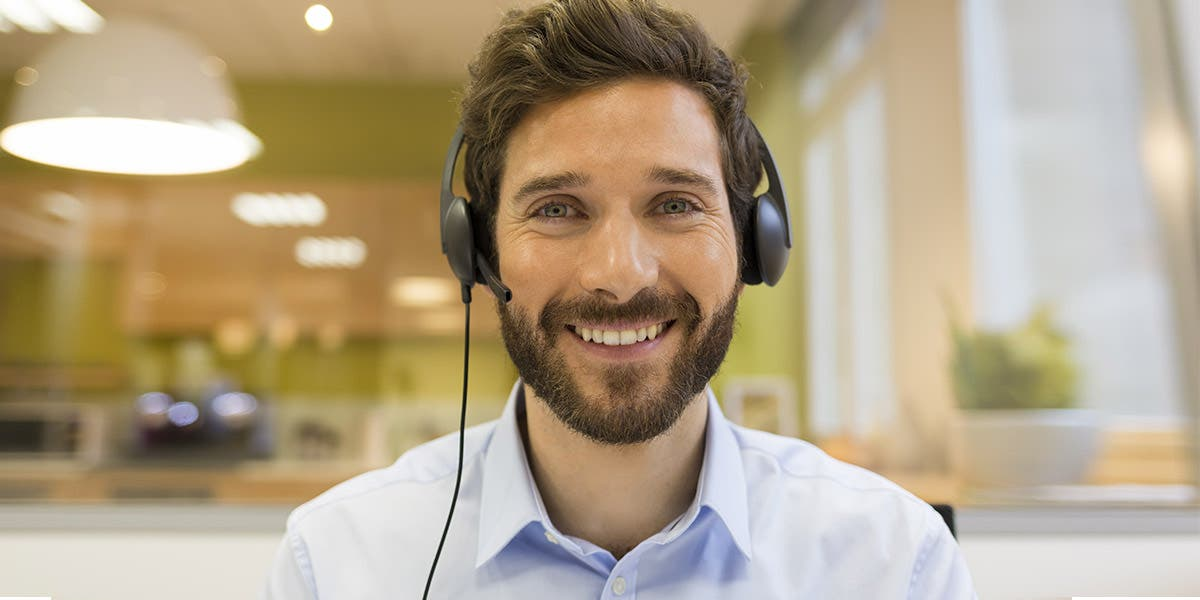 man working with a headset on, creating a successful virtual classroom experience