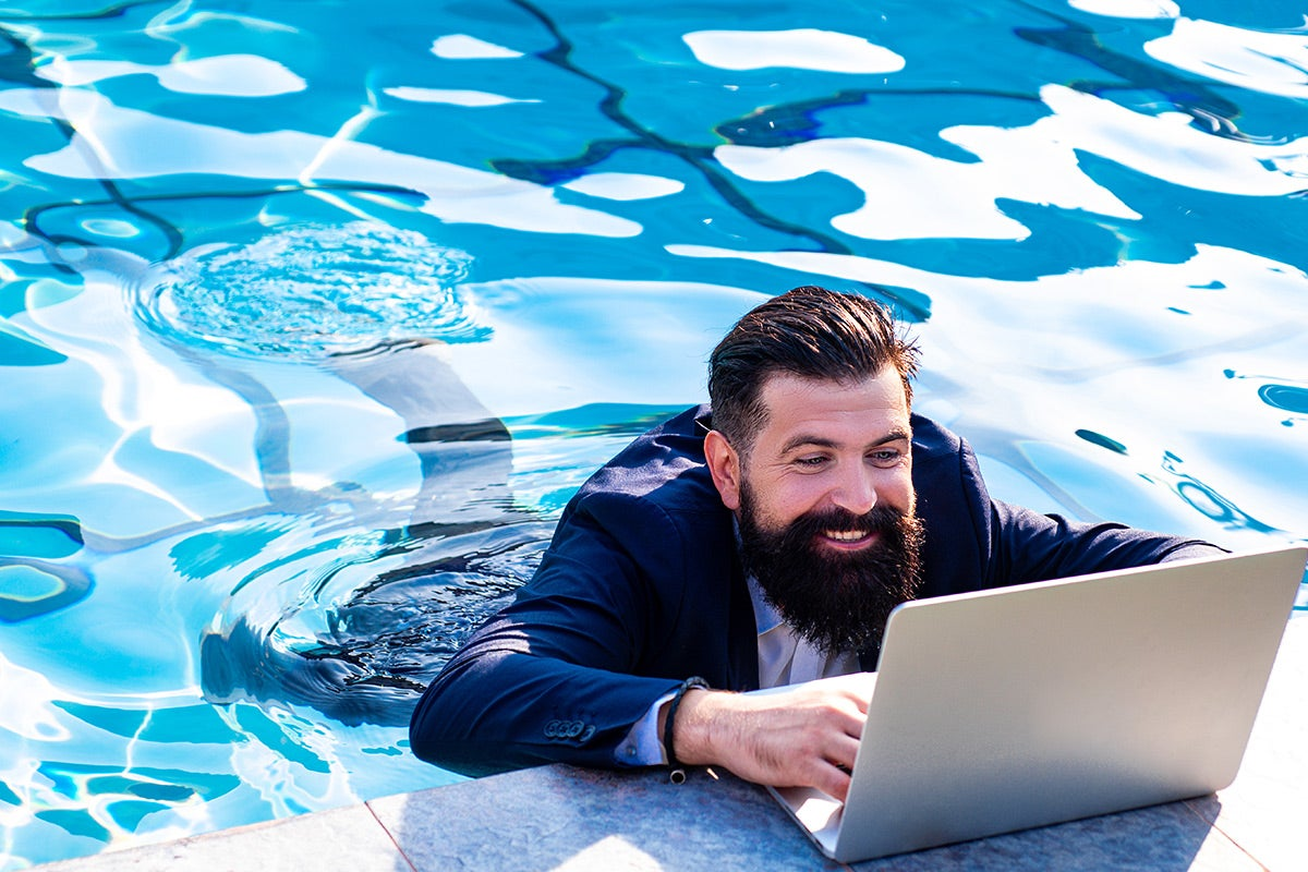 a leader in a suit working with his body in a pool and his laptop on the pool rim