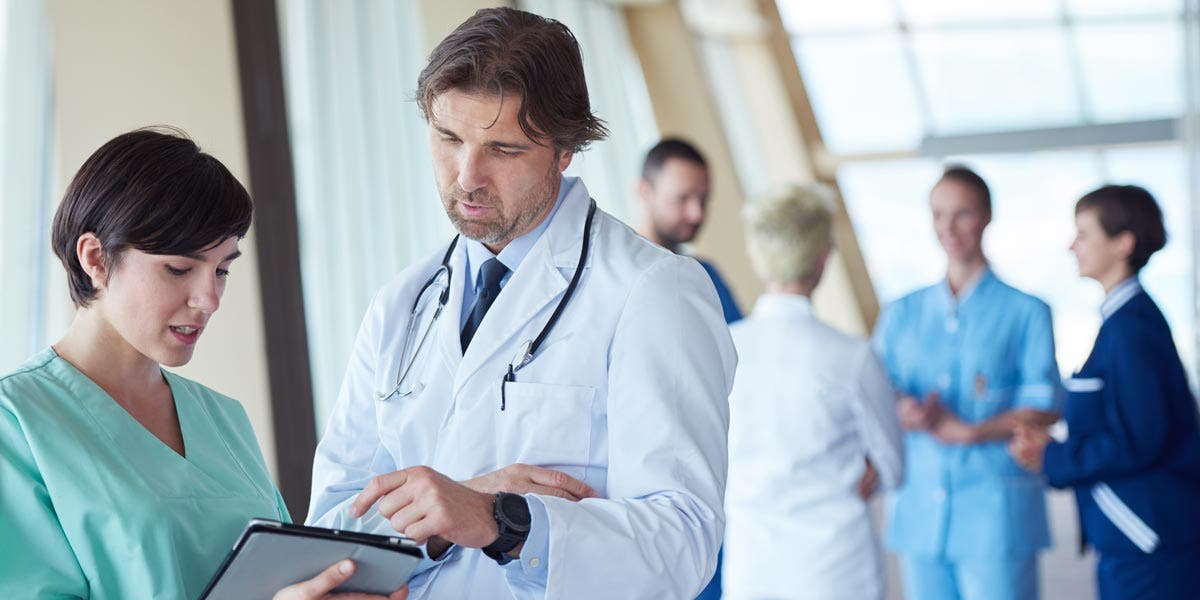 Photo representing culture change happening in healthcare with doctor and nurse having a discussion over a clipboard as colleagues chat in the background