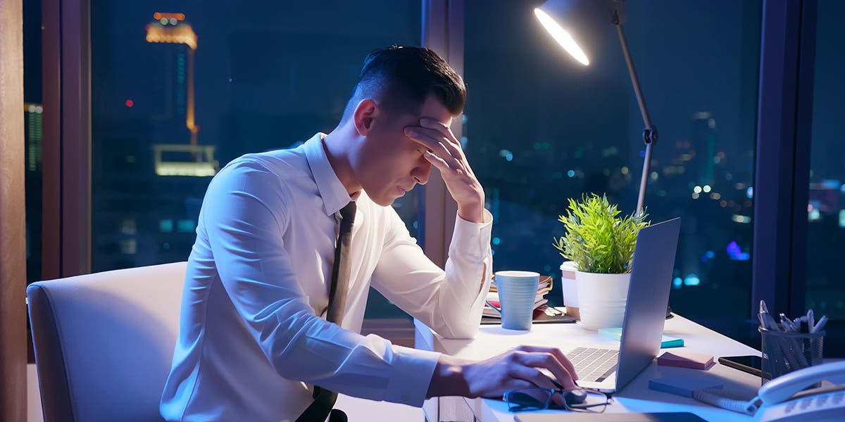frustrated new executive sitting at his desk with head in his hand to show stress over failures