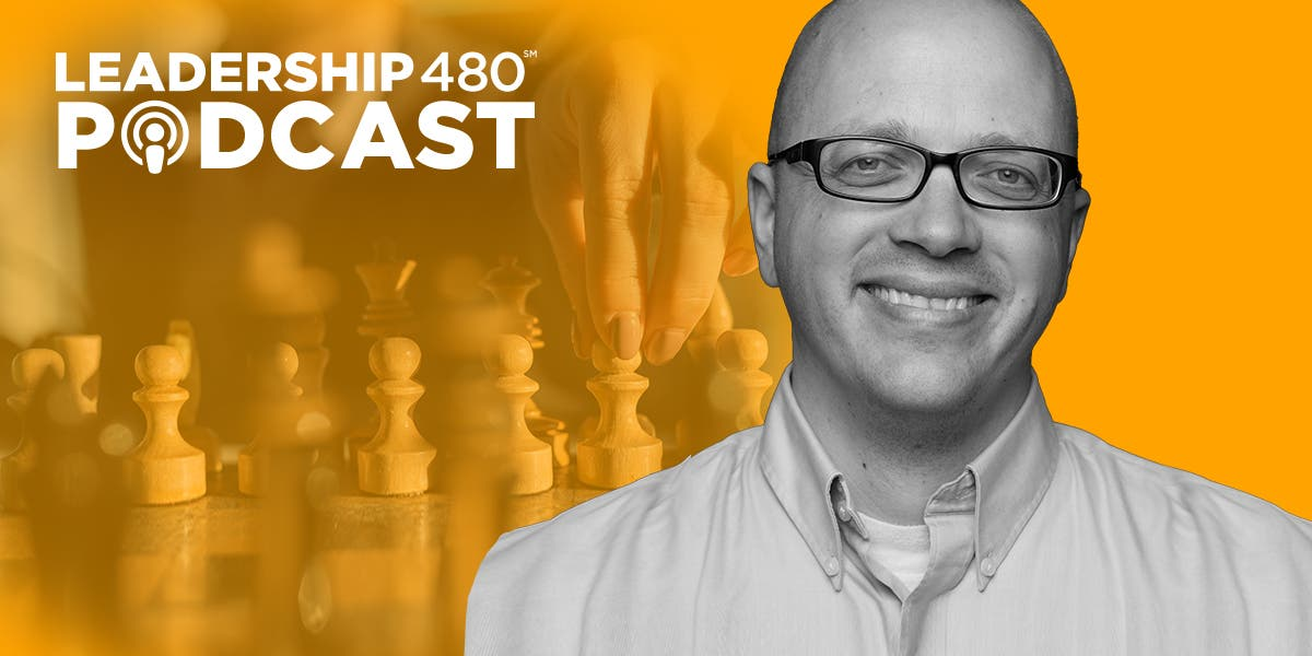 photo of Tylder Ludlow with someone moving chess pieces in the background to show that this podcast episode is about how leaders can make better decisions, and be more strategic about their decision-making process