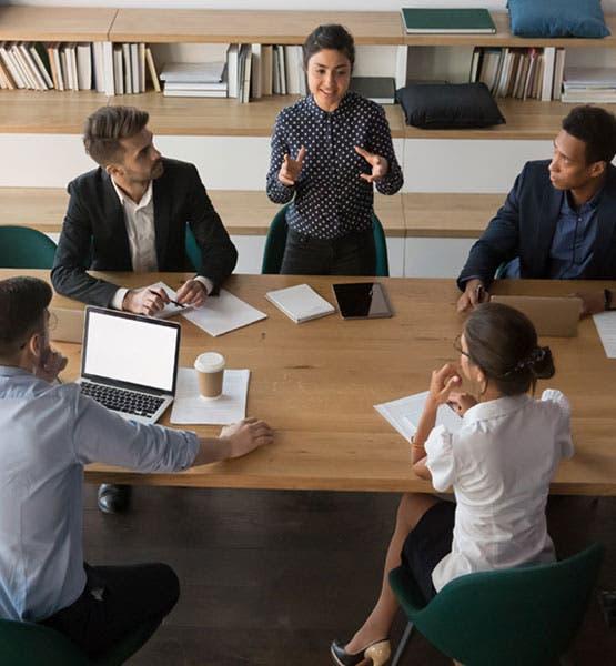 A woman standing and speaking to four team members around a conference table.?auto=format&q=75