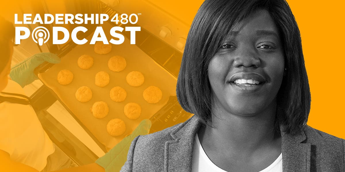 image of Leadership 480 podcast guest Hermine Dossou, with a person in the background getting a tray of cookies out of the oven to show that this episode is about leadership lessons from the Great British Baking Show