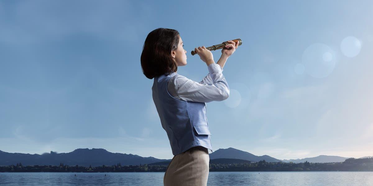 Woman looking through telescope toward the future of leadership development
