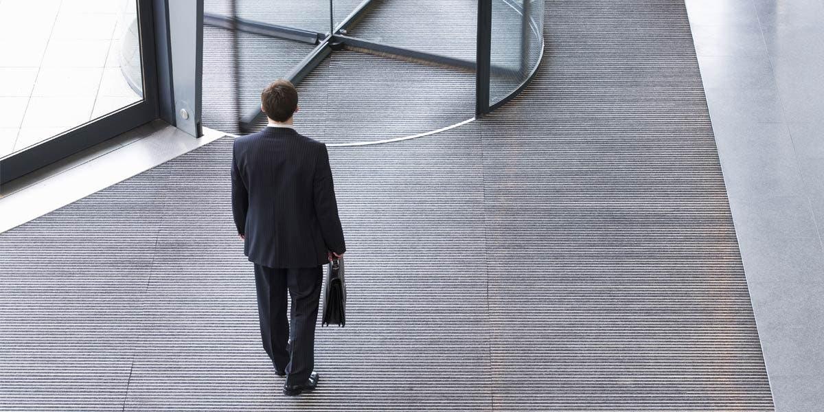 man with briefcase walking towards a revolving door