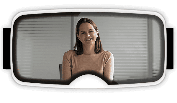 View inside of a virtual reality headset with a women sitting at a desk speaking to you?auto=format&q=75