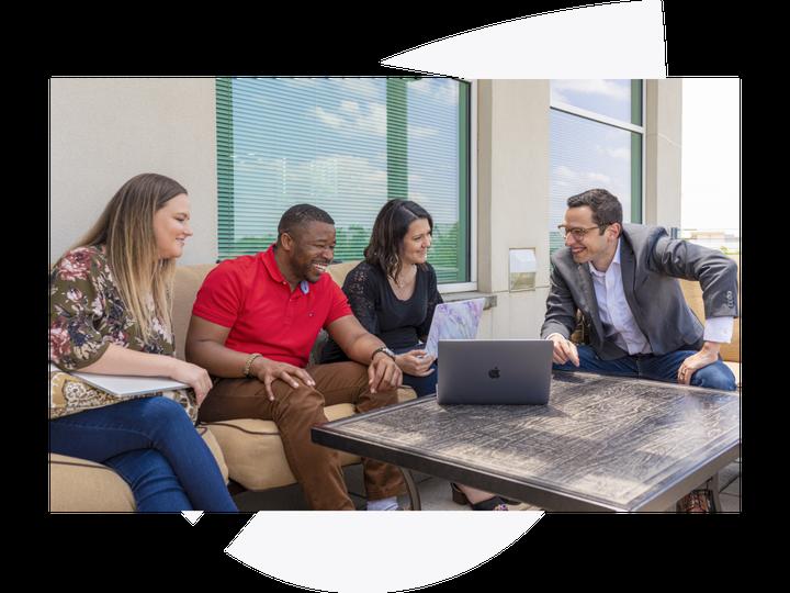 team members gathered around a laptop
