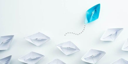 a blue paper boat among white ones