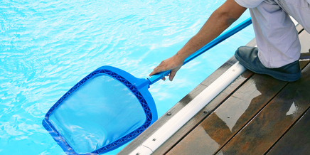 person cleaning a pool