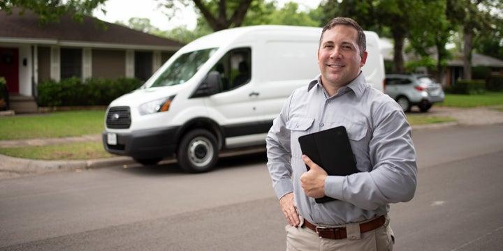 tech in front of a van