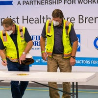 Two men in construction vests signing a paper