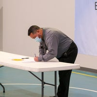 Man signing a document on a table