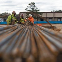 A photo shot down the side of rebar with men in the background