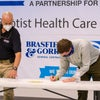 Man bent over signing a paper with another man onlooking