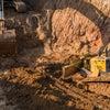 Construction digger vehicles digging dirt.