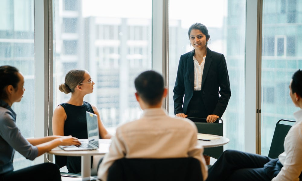 Indian Asian woman stands up in front of her diverse team and is leading a meeting, training or presentation in their office during the daytime. .jpeg
