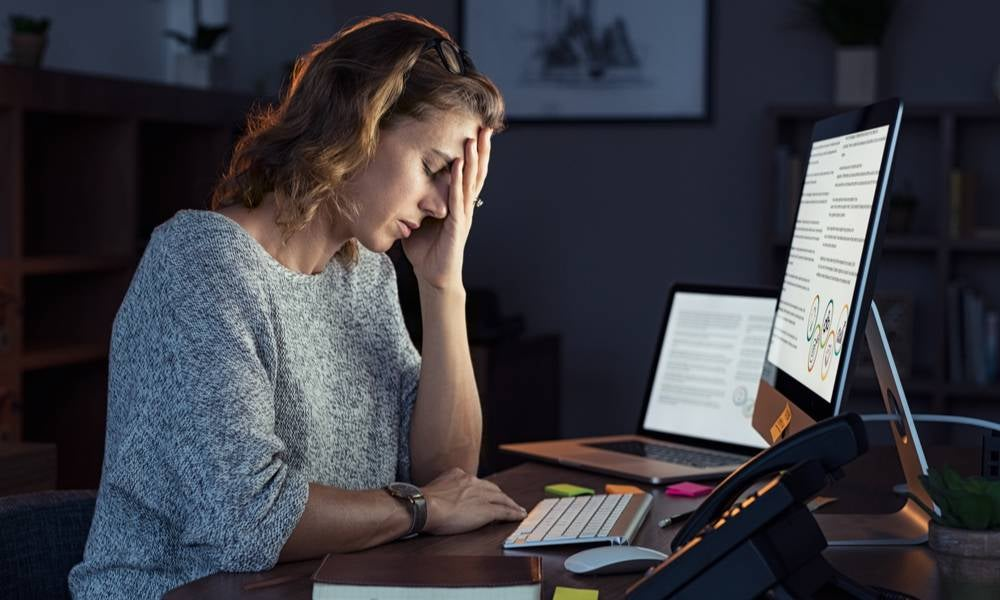 Woman working from home experiencing burnout symptoms.jpeg