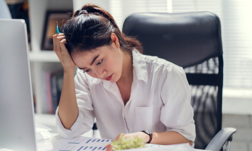 Business woman stressed at her desk mental health COVID-19-min.jpeg