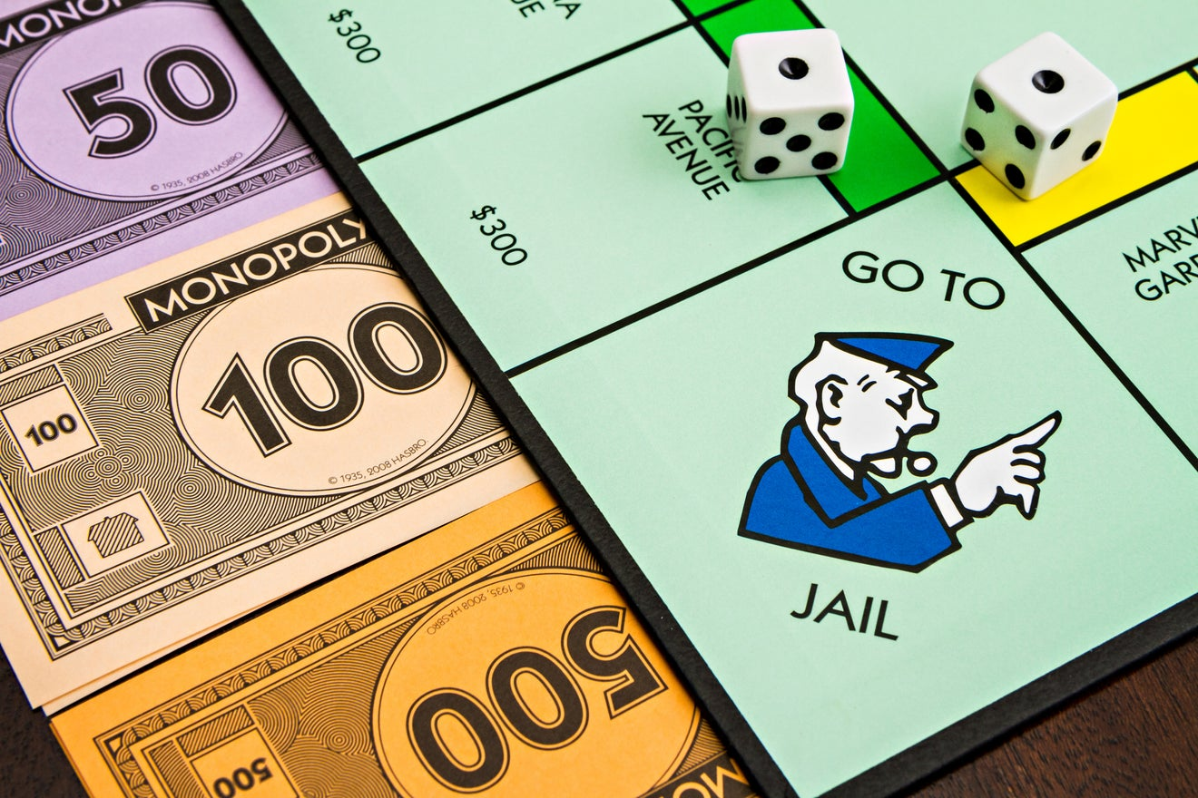 Closing tax haven loopholes. Monopoly board with money and dice featuring the 'Go To Jail' square.