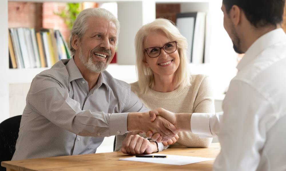 Happy senior old family couple clients make financial insurance estate business deal handshake agent lawyer.jpg