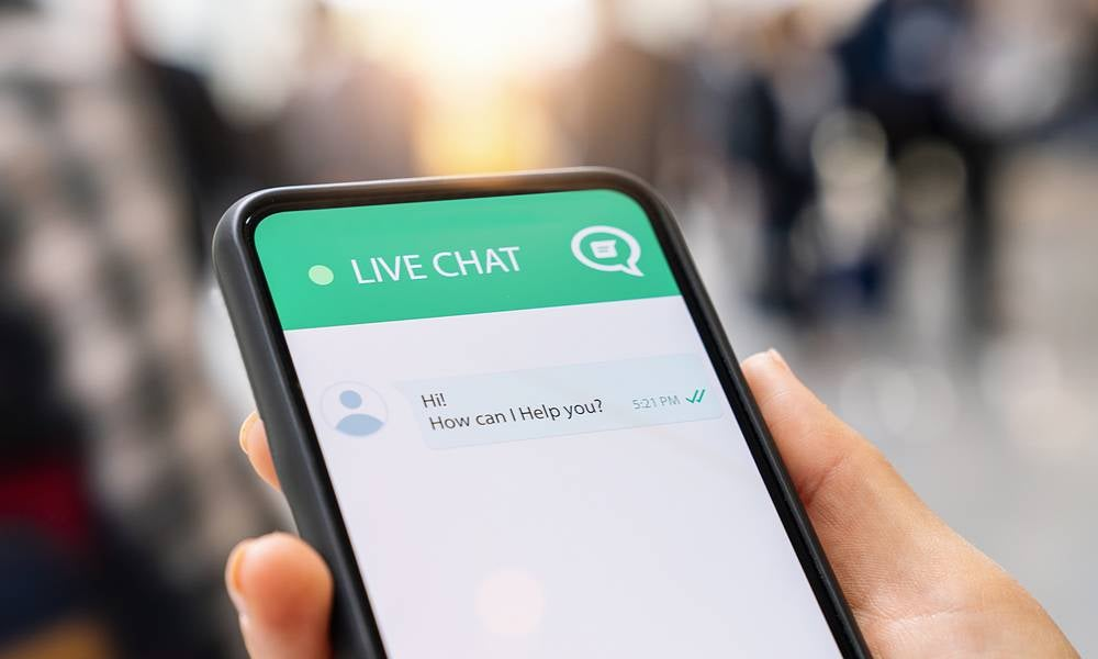 Hand holding phone screen shows live chat with AI chatbot IBM UNSW.jpeg