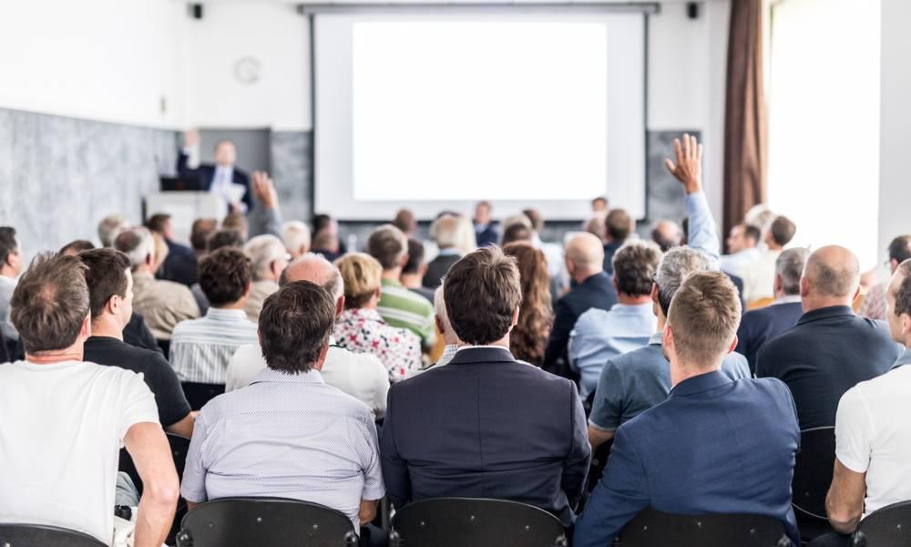 Shareholders raise hands during an annual meeting .jpeg