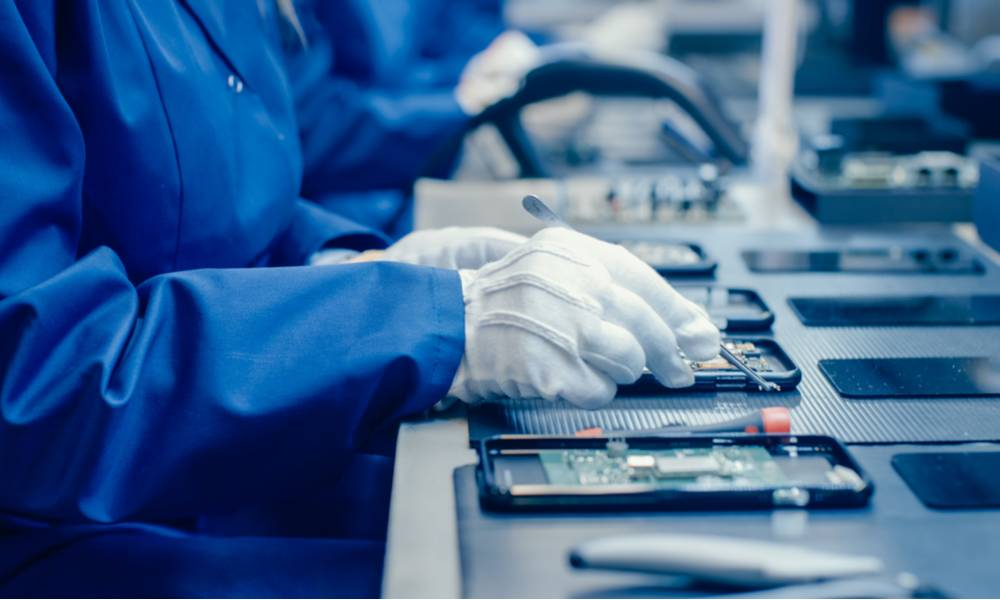 Factory worker assembling smartphones with screwdriver.jpg