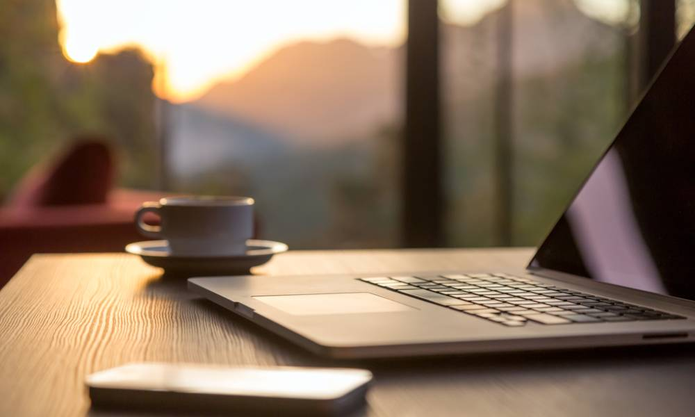 Computer and coffee mug and telephone large windows and sun rising, focus on laptop touch pad.jpg