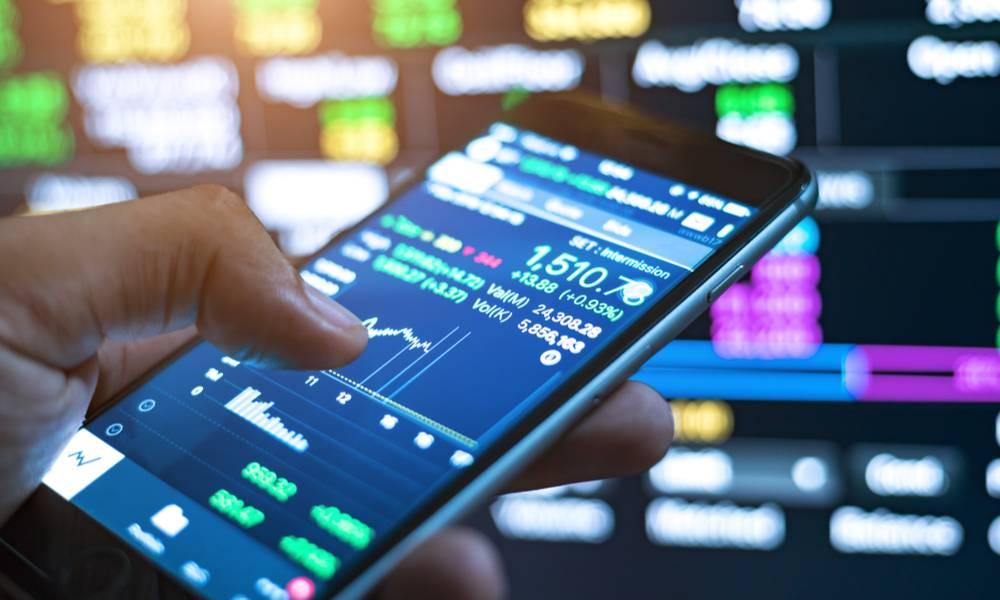 Investors hand holding phone trading online (1).jpg