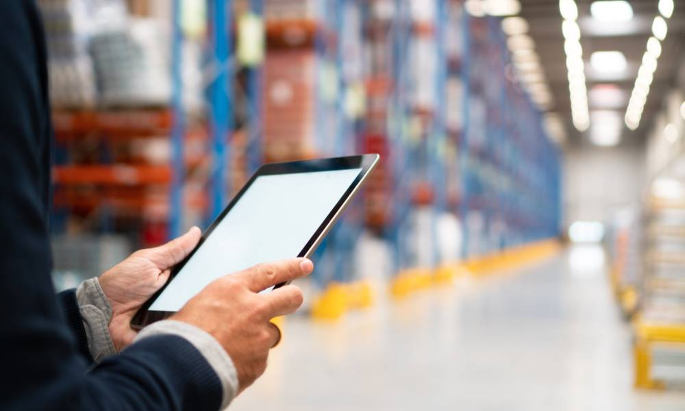 Businessman manager using tablet to manage warehouse logistics.jpg