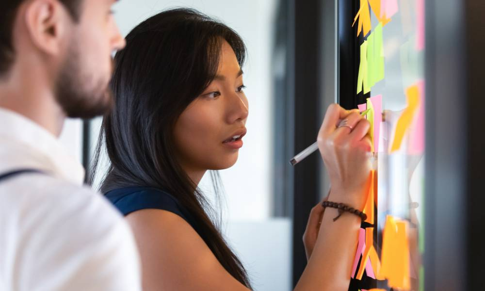 Focused business woman writing idea or task on post it sticky notes on glass wall (1).jpg