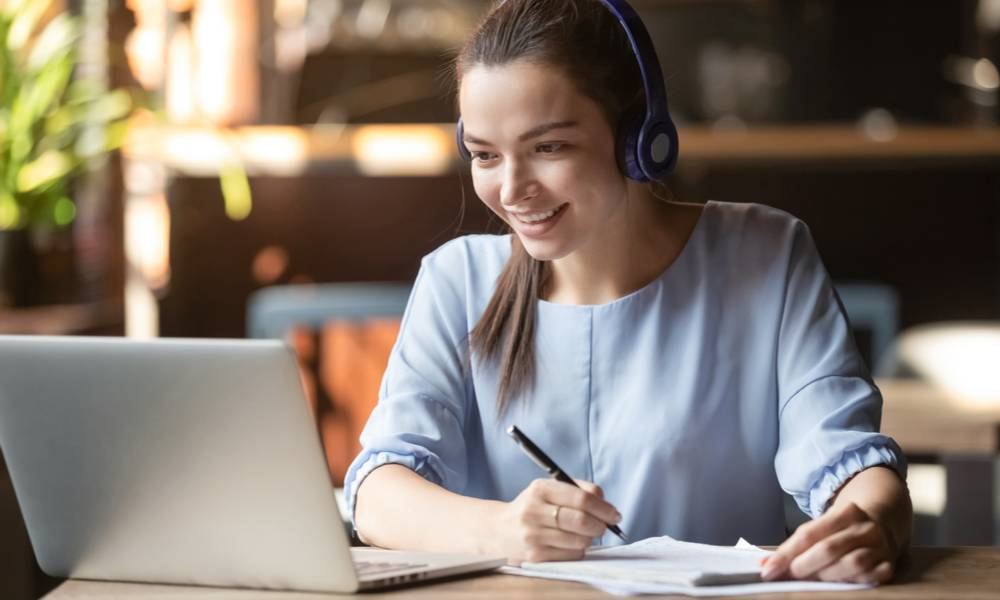 Smiling student wears wireless headphone study online with skype teacher, happy young woman learn language listen lecture watch webinar write notes look at laptop sit in cafe, distant education.jpg