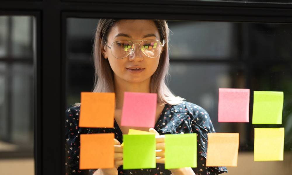 Serious focused young female coach teacher student asian business woman working on project strategy plan writing target tasks creative ideas on sticky post it notes on glass scrum board office wall.jpeg