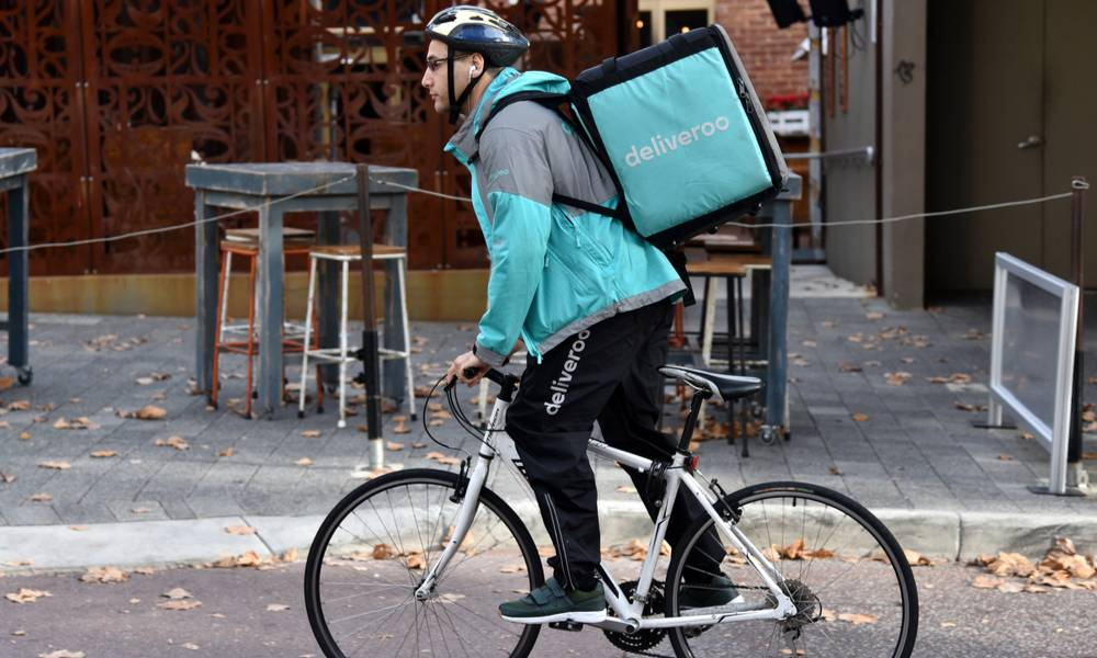 A Deliveroo rider cycles on a city centre street.jpg