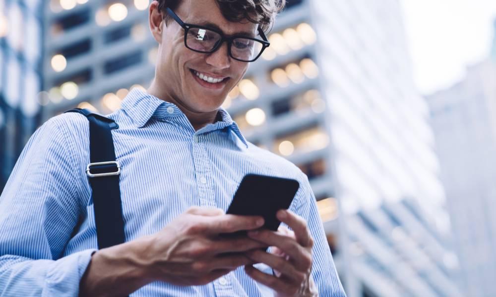 Confident employee businessman smiles at phone .jpeg