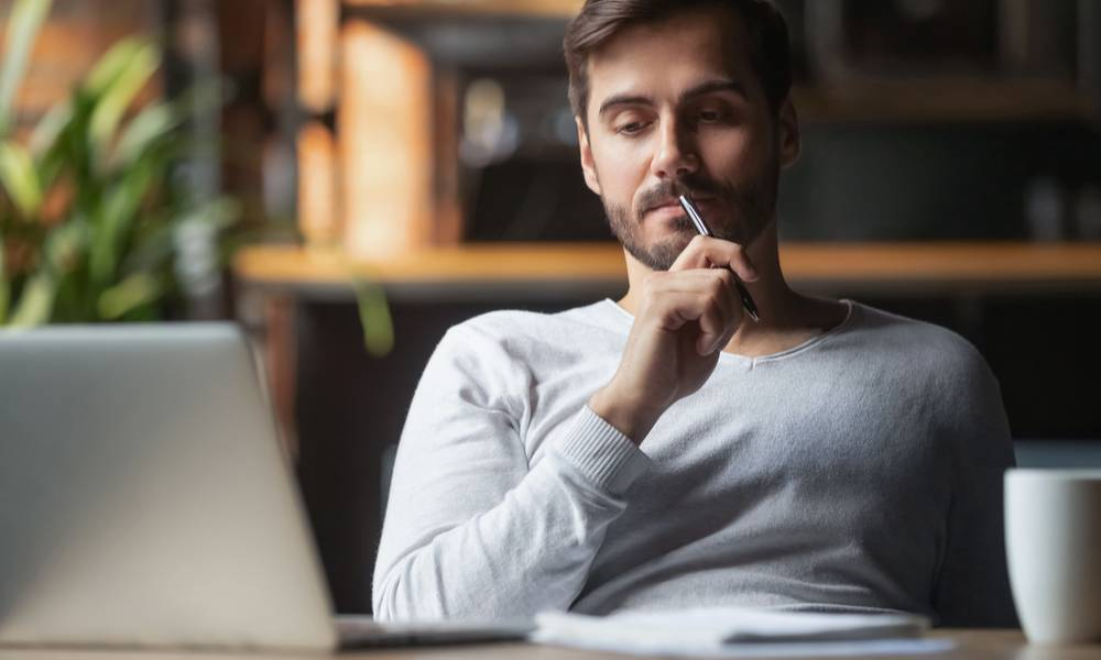 Pensive bearded man sitting at table drink coffee work at laptop thinking of problem solution (1).jpg