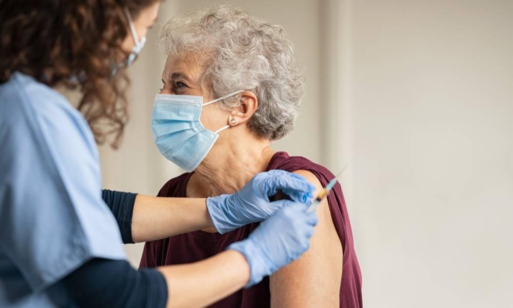 Nurse holding syringe vaccinating senior woman (1).jpg